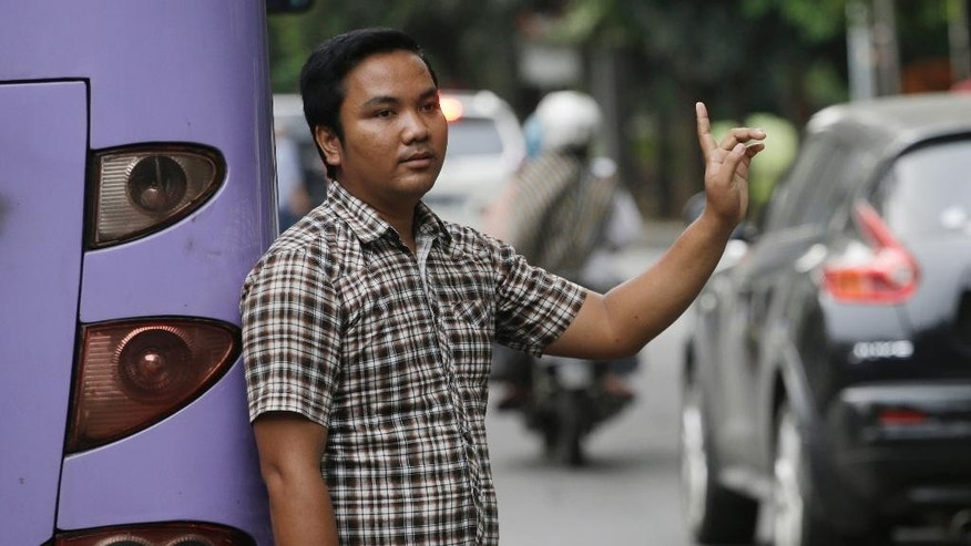 "In this Friday, April 1, 2016, photo, a man signals to show that he's for hire as a ""jockey"" to help drivers cheat a peak time traffic rule of three people to one car during rush hour, at the main business district in Jakarta, Indonesia. Traffic clogged Jakarta planned to suspend the peak time traffic rule this week raising concerns among the jockeys that they could lose their way to eke out living. (AP Photo/Achmad Ibrahim)"