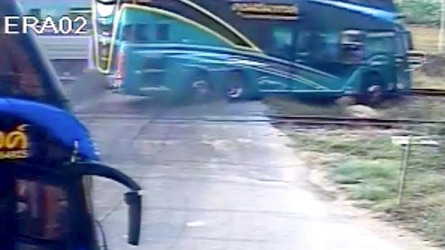 This image taken from close circuit television video provided by TPBS shows the moment a passenger train, left in background, hit a tourist bus at a crossing in Nakhon Pathom province, west of Bangkok, Thailand, Sunday, April 3, 2016. The accident occurred at about 7:30 a.m. when the double-decker bus was taking Thai tourists to Samet island in Rayong province, southeast of Bangkok. (TPBS via AP) THAILAND OUT, TV OUT, NO SALES