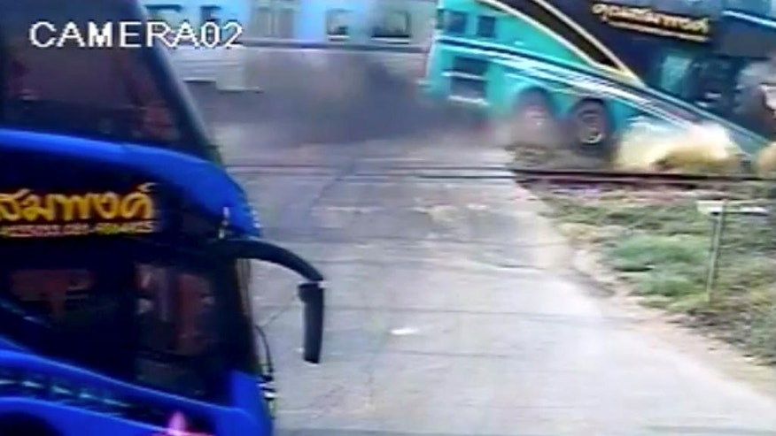 This image taken from close circuit television video provided by TPBS shows the moment a passenger train, left in background, hit a tourist bus, right, at a crossing in Nakhon Pathom province, west of Bangkok, Thailand, Sunday, April 3, 2016. The accident occurred at about 7:30 a.m. when the double-decker bus was taking Thai tourists to Samet island in Rayong province, southeast of Bangkok. (TPBS via AP) THAILAND OUT, TV OUT, NO SALES
