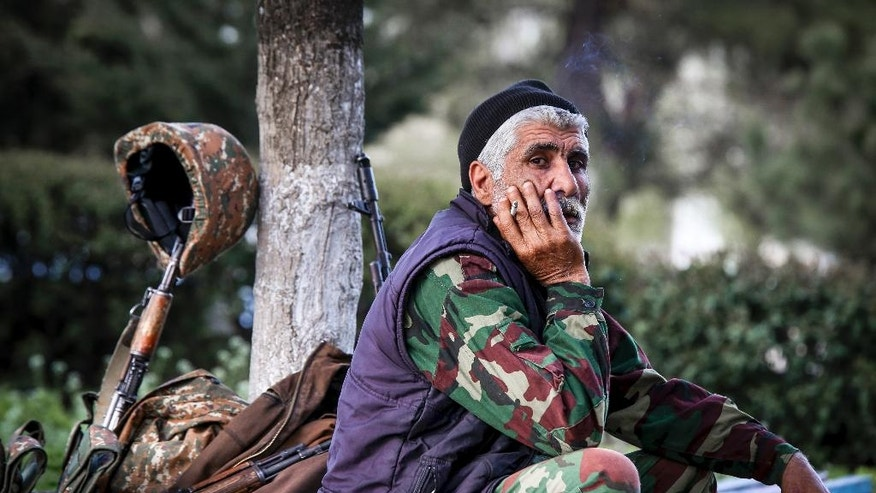 In this photo taken Saturday, April 2, 2016, an Armenian volunteer is in a state of readiness in the town of Askeran in the separatist Nagorno-Karabakh region. Officials in Azerbaijan and the separatist region of Nagorno-Karabakh say fighting is persisting a day after the worst outburst of hostilities in nearly 20 years killed 30 soldiers. Nagorno-Karabakh, part of Azerbaijan, has been under the control of local ethnic Armenian forces and the Armenian military since a war ended in 1994 with no resolution of the region's status. (Hrayr Badalyan/PAN Photo via AP)