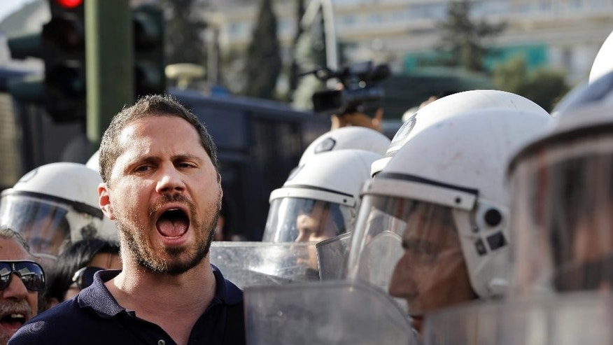 Under the watchful eye of Greek riot police officers, right, a demonstrator chants slogans during a protest against Greece's creditors in Athens, Monday, April 4, 2016, as Greece's government started new talks with bailout creditors amid a dispute over a wiretapped and leaked conversation between foreign officials involved in the Greek bailout negotiations. The main sticking points are mandated pension cuts, tax reforms and future cuts Greece must make to meet bailout targets. The country has depended on bailouts since 2010. (AP Photo/Lefteris Pitarakis)