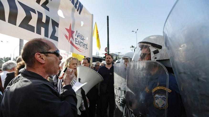 Under the watchful eye of Greek riot police officers, right, demonstrators chant slogans during a protest against Greece's creditors in Athens, Monday, April 4, 2016, as Greece's government started new talks with bailout creditors amid a dispute over a wiretapped and leaked conversation between foreign officials involved in the Greek bailout negotiations. The main sticking points are mandated pension cuts, tax reforms and future cuts Greece must make to meet bailout targets. The country has depended on bailouts since 2010. (AP Photo/Lefteris Pitarakis)