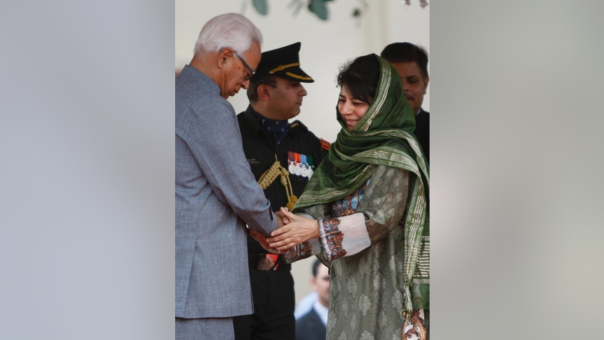 New Indian Kashmir Chief Minister Mehbooba Mufti, right, shakes hands with Jammu and Kashmir Gov. N.N. Vohra after she took the oath of office during a ceremony administered by Vohra in Jammu, India, Monday, April 4, 2016. Mufti, the leader of a pro-India party, on Monday became the first woman to become the chief minister of Indian Kashmir following the death of her father, the region's top elected leader. Mufti took the oath on Monday after her Peoples' Democratic Party and India's ruling Bharatiya Janata Party ended a nearly three-month deadlock over forming the state government. (AP Photo/Channi Anand)