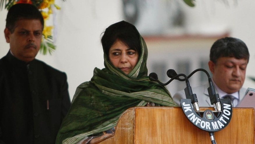 New Indian Kashmir Chief Minister Mehbooba Mufti, center, takes the oath of office during a ceremony in Jammu, India, Monday, April 4, 2016. Mufti, the leader of a pro-India party, on Monday became the first woman to become the chief minister of Indian Kashmir following the death of her father, the region's top elected leader. Mufti took the oath on Monday after her Peoples' Democratic Party and India's ruling Bharatiya Janata Party ended a nearly three-month deadlock over forming the state government. (AP Photo/Channi Anand)