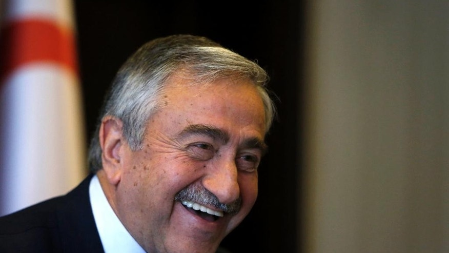 Turkish Cypriot leader Mustafa Akinci smiles is seen at his office during an interview for the Associated Press in the Turkish breakaway north part of the divided capital Nicosia in this ethnically Mediterranean island of Cyprus, Monday, April 4, 2016.  The leader of the breakaway Turkish Cypriots says the ethnically divided island's potential wealth from newly found offshore gas deposits could partly pay for a costly reunification deal. (AP Photo/Petros Karadjias)