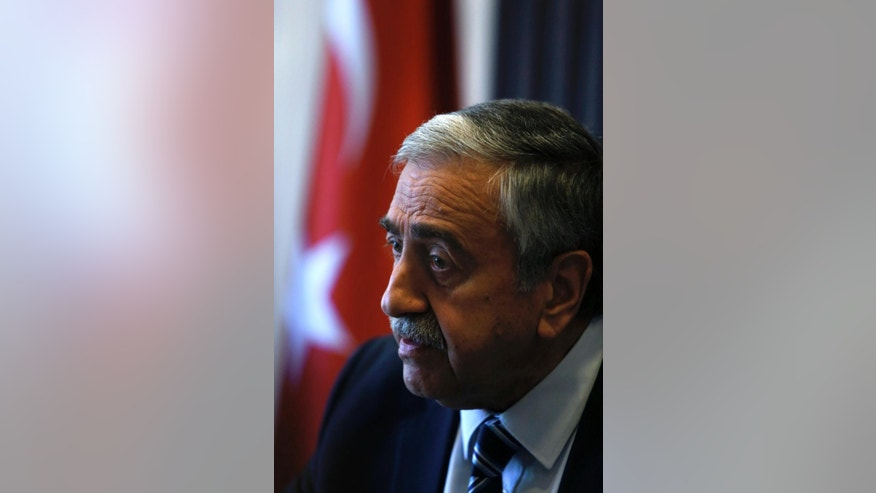 Turkish Cypriot leader Mustafa Akinci is seen at his office during an interview for the Associated Press in the Turkish breakaway north part of the divided capital Nicosia in this ethnically Mediterranean island of Cyprus, Monday, April 4, 2016. The leader of the breakaway Turkish Cypriots says the ethnically divided island's potential wealth from newly found offshore gas deposits could partly pay for a costly reunification deal. (AP Photo/Petros Karadjias)