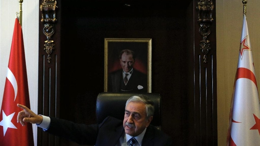 Turkish Cypriot leader Mustafa Akinci is seen at his office in front of the portrait of the Turkish Republic founder Kemal Ataturk, during an interview for the Associated Press in the Turkish breakaway north part of the divided capital Nicosia in this ethnically Mediterranean island of Cyprus, Monday, April 4, 2016. The leader of the breakaway Turkish Cypriots says the ethnically divided island's potential wealth from newly found offshore gas deposits could partly pay for a costly reunification deal. (AP Photo/Petros Karadjias)