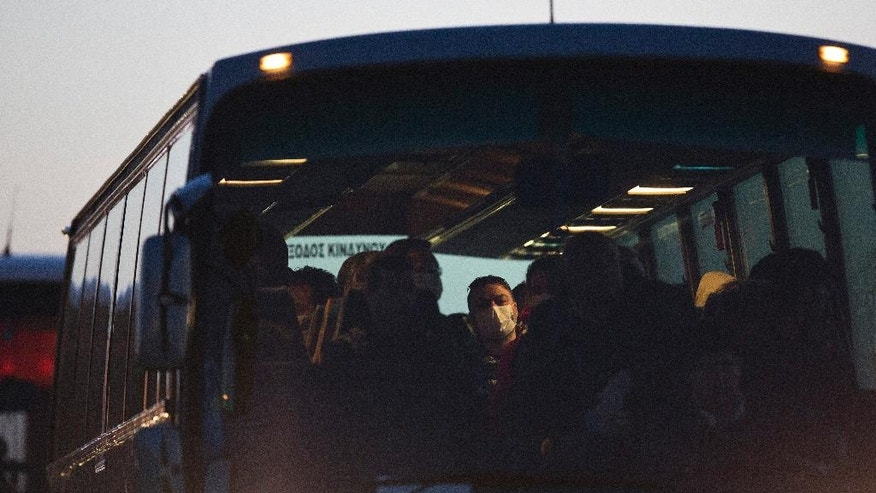 Migrants arrive with a bus at the port of Mytilini in the Greek island of Lesbos, Monday, April 3, 2016, during the first day of the  implementation of the deal between EU and Turkey. Under the deal, migrants arriving illegally in Greece will be returned to Turkey if they do not apply for asylum or if they make an asylum claim that is rejected.(AP Photo/Petros Giannakouris)