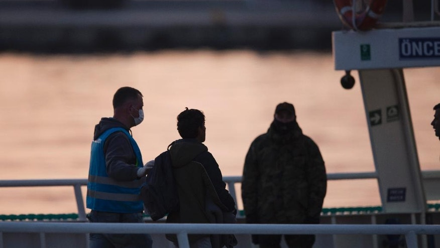 A Frontex personnel leads a migrant in a ferry for Turkey at the port of Mytilini in the Greek island of Lesbos, Monday, April 4, 2016, during the first day of the implementation of the deal between EU and Turkey. Under the deal, migrants arriving illegally in Greece will be returned to Turkey if they do not apply for asylum or if they make an asylum claim that is rejected.(AP Photo/Petros Giannakouris)