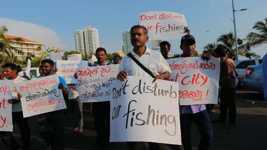 "Sri Lankan fishermen carry placards during a protest in Colombo, Sri Lanka, Monday, April 4, 2016. Hundreds of people, including priests, environmental activists and fishermen, protested in Sri Lanka's capital on Monday, demanding the government halt a $1.5 billion Chinese-funded port city project. Placard on left reads, ""Prime minister please keep your promise to stop the port city project""  as other placards in Sinhalese language carry slogans urging the government to stop the project. (AP Photo/Eranga Jayawardena)"