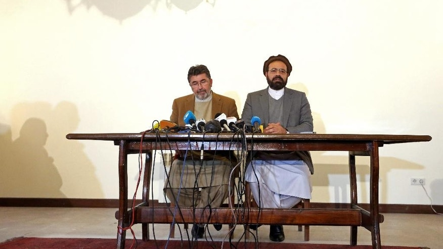 In this March 17, 2016 photo, Amin Karim, right, an official of the Hezb-i-Islami Party, speaks during a press conference in Kabul, Afghanistan. According to Karim, the party's leader, Gulbuddin Hekmatyar,  a notorious Afghan warlord who lives in hiding, has dropped a key condition for ending his war of more than 40 years with Kabul, no longer demanding that all foreign troops leave Afghanistan. (AP Photo/Rahmat Gul)