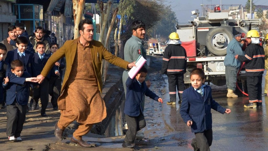 FILE -- In this Jan. 13, 2016 file photo, an Afghan teacher, in brown, helps school children run from the site of clashes near the Pakistan consulate in Jalalabad, capital of Nangarhar province, Afghanistan. One of Afghanistan's proudest achievements has been getting millions of children, especially girls, back into school since the toppling of the Taliban, but that gain is crumbling across the south and in other war-torn parts of the country. Hundreds of schools have been forced to shut down because of fighting or Taliban intimidation.  (AP Photos/Mohammad Anwar Danishyar, File)