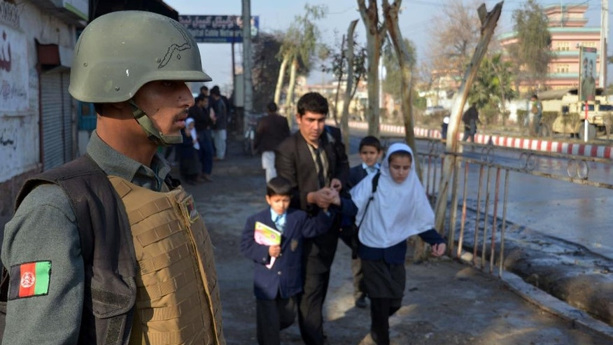 FILE -- In this Jan. 13, 2016 file photo, an Afghan member of the security forces stands guard as a man helps school children run from the site of clashes near Pakistan's consulate in Jalalabad, capital of Nangarhar province, Afghanistan. One of Afghanistan's proudest achievements has been getting millions of children, especially girls, back into school since the toppling of the Taliban, but that gain is crumbling across the south and in other war-torn parts of the country. Hundreds of schools have been forced to shut down because of fighting or Taliban intimidation. (AP Photos/Mohammad Anwar Danishyar, File)