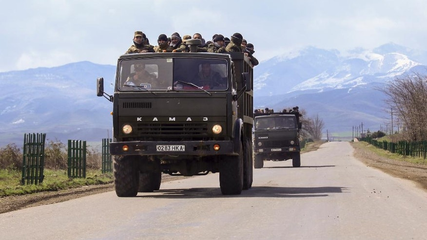 Ethnic Armenian fighters stand in backs of Kamaz military trucks on their way to a frontline at Martakert province in the separatist region of Nagorno-Karabakh, Azerbaijan, Monday, April 4, 2016. Fighting raged Monday around Nagorno-Karabakh, with Azerbaijan saying it lost three of its troops in the separatist region while inflicting heavy casualties on Armenian forces and the Armenian president warning that the hostilities could slide into a full-scale war. (Hrayr Badalyan, PAN Photo via AP)