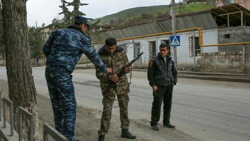 Ethnic Armenian fighters armed with a Kalashnikov machine gun stand at their positions on a road at Martakert province in the separatist region of Nagorno-Karabakh, Azerbaijan, Monday, April 4, 2016. Fighting raged Monday around Nagorno-Karabakh, with Azerbaijan saying it lost three of its troops in the separatist region while inflicting heavy casualties on Armenian forces and the Armenian president warning that the hostilities could slide into a full-scale war. (Vahan Stepanyan, PAN Photo via AP)