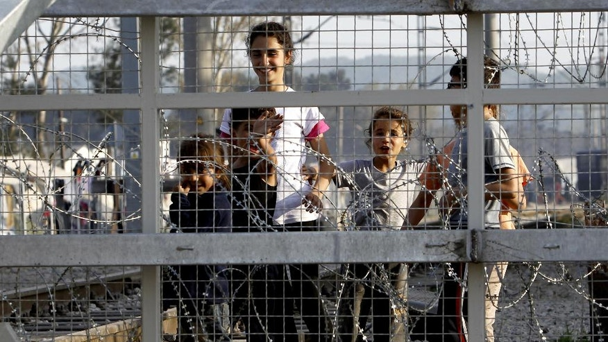 Children play behind the fence, in a makeshift camp at Idomeni border station on the Greek side of the border with Macedonia, photographed from the Macedonian side of the border line Monday, April 4, 2016. The European Union plan to contain the refugee crisis took a major step on Monday with the returns to Turkey of 202 migrants and refugees who had not applied for asylum in Greece. (AP Photo/Boris Grdanoski)