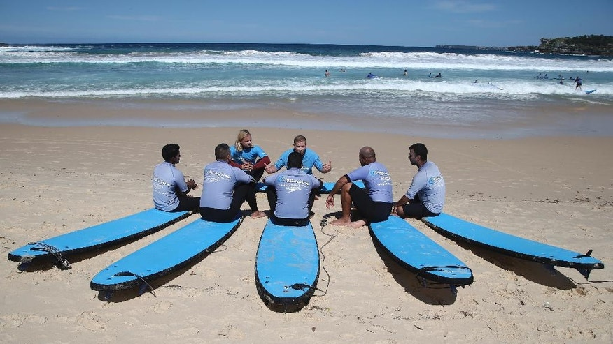 In this Wednesday, March 23, 2016, photo, five asylum seekers sit on their surfboards at the beginning of a surfing class on Bondi Beach in Sydney, Australia. A novel program by the not-for-profit organization Settlement Services International is introducing the asylum seekers to the iconic Aussie sport of surfing in a bid to transform their feelings toward the ocean and their lives. (AP Photo/Rob Griffith)