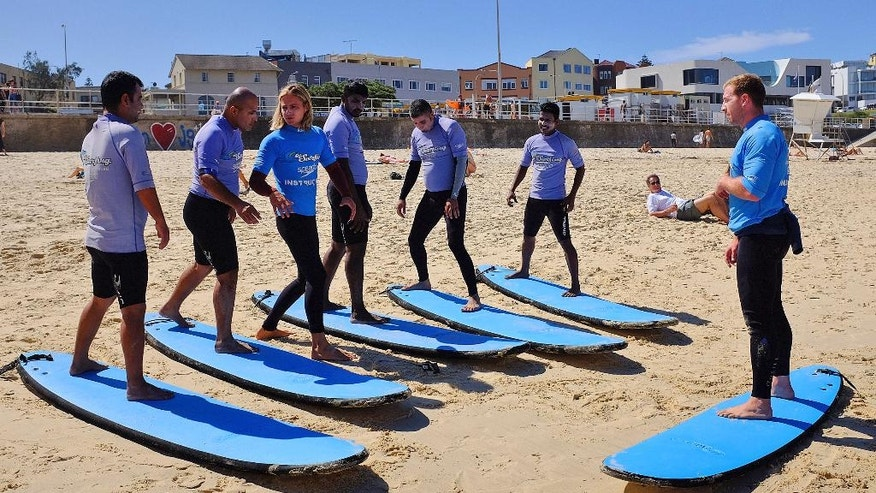 In this Wednesday, March 23, 2016, photo, five asylum from left, Roohollah, Amin, surf instructor Conrad Pattinson, Uthayakumar, Mahdi, Kumar and surf instructor Will Bigelow practice standing on their surfboards while still on the sand during a surfing class on Bondi Beach in Sydney, Australia. A novel program by the not-for-profit organization Settlement Services International is introducing asylum seekers to the iconic Aussie sport of surfing in a bid to transform their feelings toward the ocean and their lives. (AP Photo/Rob Griffith)