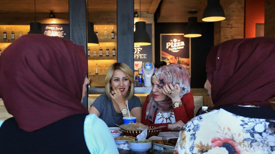 In this Sunday, April 3, 2016 photo, Iraqis have lunch at a restaurant in Baghdad, Iraq. The food business is booming, despite the war and an economic slump, as entrepreneurs find restaurants and eateries a safe business bet. Baghdad's expanding restaurant scene is unexpected in a city facing almost daily bombings, and a nation embroiled in political crisis. (AP Photo/Karim Kadim)