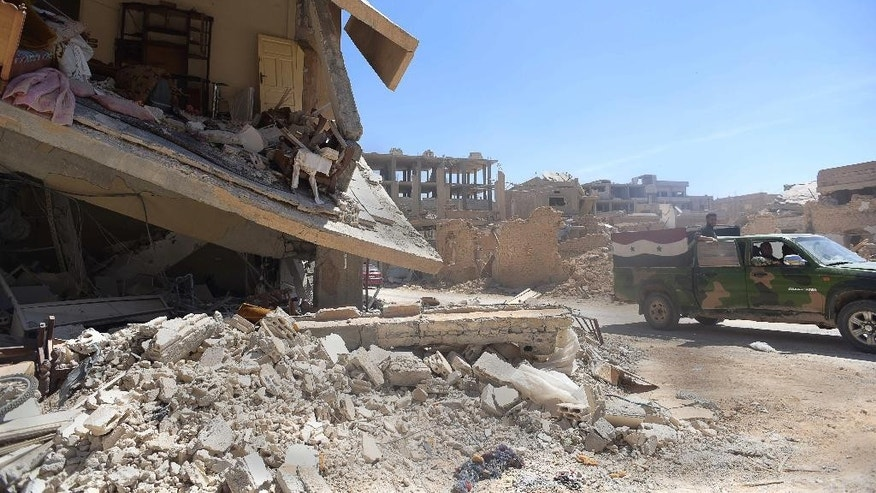 Syrian soldiers pass through a heavily damaged area after their victory against the Islamic State group in Qaryatain, Syria, Monday, April 4, 2016. Syrian troops and allied militiamen pressed on with an offensive against Islamic State militants in central Syria on Monday, clashing with the extremists around the town of Qaryatain a day after it was captured by pro-government forces.(AP Photo/Natalia Sancha)