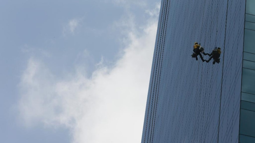 "A building window cleaner works on a building in Panama City's Banking area, Monday, April 4, 2016. Panama's president says his government will cooperate ""vigorously"" with any judicial investigation arising from the leak of a vast trove of information on the offshore financial dealings of the world's rich and famous. An international coalition of media outlets Sunday published investigations it said stemmed from the leak of 115 million records kept by the Panama-based law firm Mossack Fonseca on behalf of clients. (AP Photo/Arnulfo Franco)"