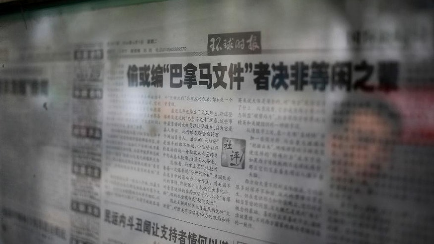 "A man walks past the nationalistic tabloid Global Times' editorial on ""Panama reports"" displayed on a newspaper board in Beijing, Tuesday, April 5, 2016. China's Foreign Ministry on Tuesday denounced as ""groundless"" reports based on documents leaked from a Panama-based law firm that name relatives of current and retired Chinese politicians, including President Xi Jinping, as owning offshore companies. The Global Times' editorial said an unidentified ""powerful force"" was behind the document leak. It said the main targets were opponents of the West, especially Russian President Vladimir Putin. (AP Photo/Andy Wong)"