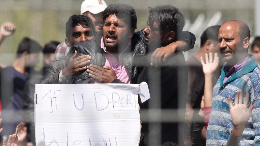 Refugees and  migrants most of them from Pakistan protest against EU- Turkey deal about migration inside the entrance of Moria camp in the Greek island of Lesbos on Tuesday, April 5, 2016, Authorities in Greece have paused deportations to Turkey and acknowledged that most migrants and refugees detained on the islands have applied for asylum. (AP Photo/Petros Giannakouris)