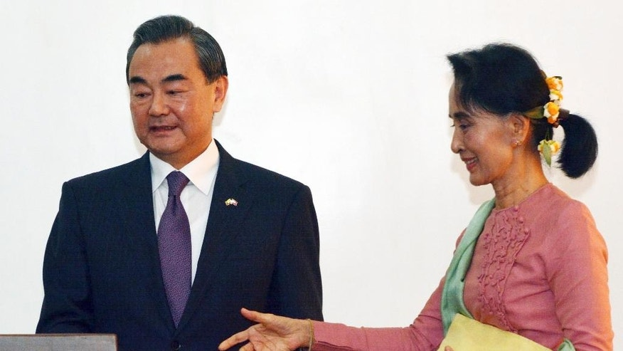 Leader of the National League for Democracy party (NLD) and Myanmar's new Foreign Minister Aung San Suu Kyi, right, and Chinese Foreign Minister Wang Yi reach a podium for their joint press conference in Naypyitaw, Myanmar, Tuesday, April 5, 2016. (AP Photo/Aung Shine Oo)