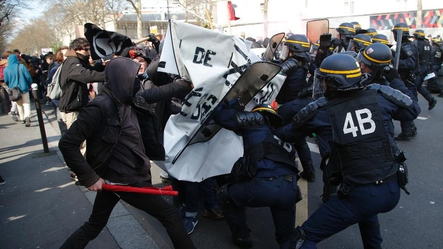 Riot police officers scuffle with youth  during a demonstration in Paris, Tuesday, April 5, 2016. Unions call on French teachers, transport workers and others to join a strike and protests against a bill extending the workweek and making layoffs easier. (AP Photo/Michel Euler)