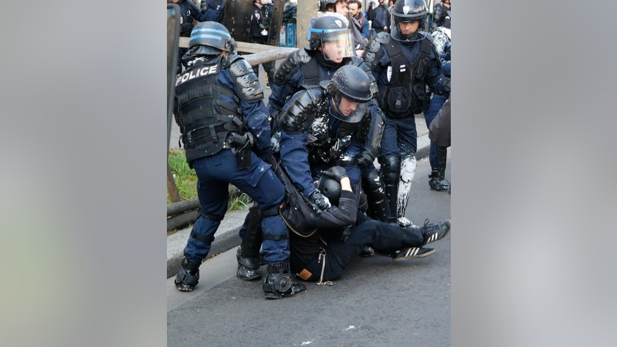 Riot police officers detain a protestor during a demonstration in Paris, Tuesday, April 5, 2016. Unions call on French teachers, transport workers and others to join a strike and protests against a bill extending the workweek and making layoffs easier. (AP Photo/Michel Euler)