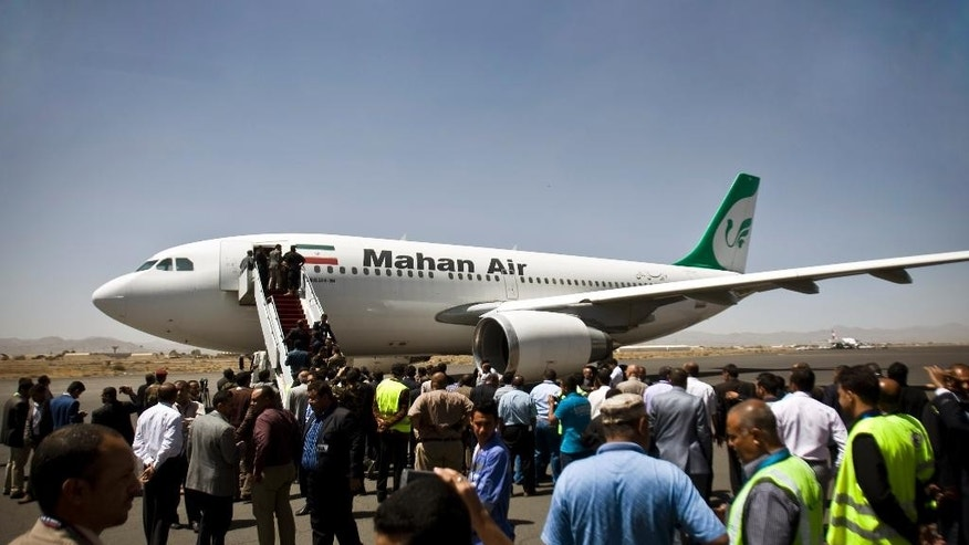 """FILE -- In this March 1, 2015 file photo, Yemeni airport, security and transportation officials greet a plane from the Iranian private airline, Mahan Air after it lands in Sanaa, Yemen. Saudi Arabia's General Authority of Civil Aviation issued an order in a statement Monday, April 4, 2016, that banned Mahan Air from flying into the kingdom  over """"systematic violations"""" of the country's safety regulations and laws as tensions between the two Mideast powers remain high. (AP Photo/Hani Mohammed, File)"""