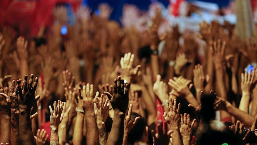 Supporters raise their arms during a rally in support of Brazil's former President Luiz Inacio Lula da Silva and President Dilma Rousseff, in Sao Bernardo do Campo, in the greater Sao Paulo area, Brazil, Monday, April 4, 2016. President Rousseff is currently facing impeachment proceedings and Lula da Silva has been linked to a sprawling corruption scandal involving Brazilian oil giant Petrobras. (AP Photo/Andre Penner)
