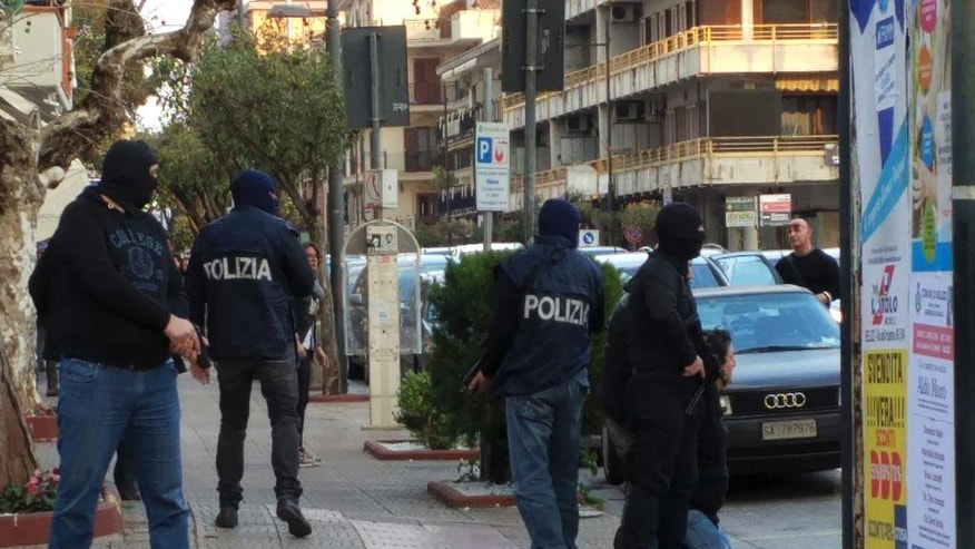 In this photo taken on Saturday, March 26,  and made available on Sunday, May 27, 2016, Italian Police arrest a man, kneeling at right, in the southern city of Bellizzi, near Salerno, Italy. Police identified the man detained as Djamal Eddine Ouali, an Algerian wanted in Belgium for facilitating illegal migration linked to the recent terror attacks in Paris. According to police he was sought under a European arrest warrant for alleged involvement in a network in Brussels which makes false documents, including those used by extremists implicated in the Paris and Brussels attacks.  Your lost or stolen passport may have found a new life in the shady underworld of a crime gang or in the pocket of a terrorist plotting an attack, like the strikes in Paris or the Brussels bombings. (Carmine Cappetti/www.asalerno.it via AP Photo) MANDATORY CREDIT
