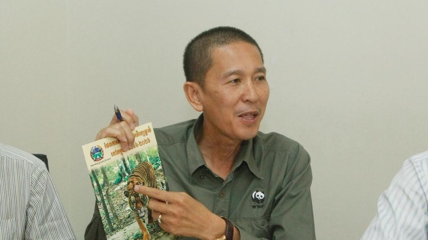Chhith Sam Ath, Cambodia Director of  World Wildlife Fund, WWF, shows a booklet  during a press conference, in Phnom Penh, Cambodia, Wednesday, April 6, 2016.  Cambodia has unveiled a plan to reintroduce tigers from abroad into the dry forests of the country, where they have become virtually extinct due to poaching. (AP Photo/Heng Sinith)