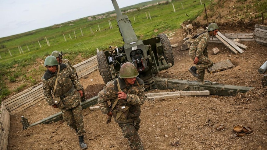 Nagorno-Karabakh army artillerymen prepare to open fire from a howitzer on positions in Nagorno-Karabakh, Azerbaijan, Tuesday, April 5, 2016. Azerbaijan forces and separatist forces in Nagorno-Karabakh agreed on a cease-fire Tuesday following three days of the heaviest fighting in the region since 1994, the Azeri defense ministry announced. (Vahan Stepanyan/PAN Photo via AP)