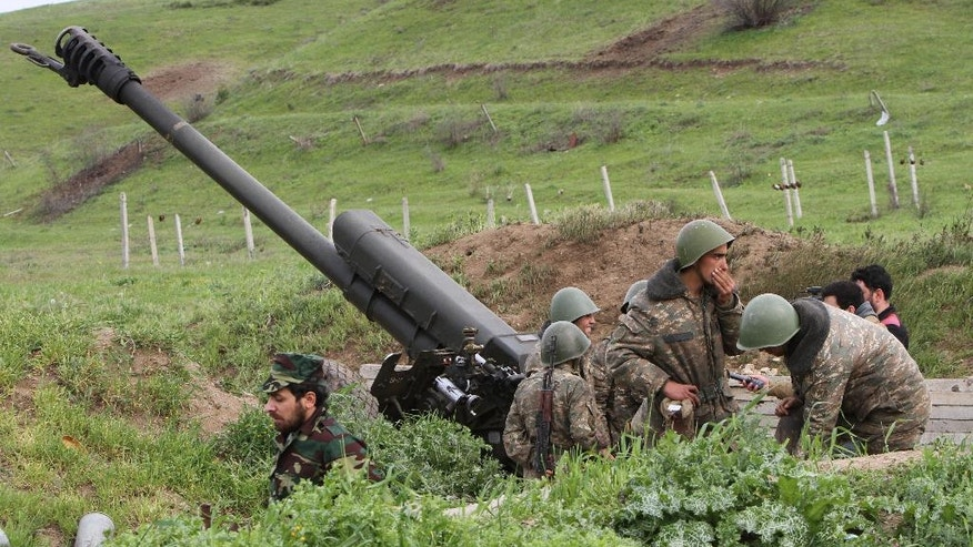 Karabakh Armenian soldiers stand near a howitzer in Hadrut province in Nagorno-Karabakh, Azerbaijan, Tuesday, April 5, 2016. Azerbaijan forces and separatist forces in Nagorno-Karabakh agreed on a cease-fire Tuesday following three days of the heaviest fighting in the region since 1994, the Azeri defense ministry announced. (Albert Khachatryan/Photolure via AP)
