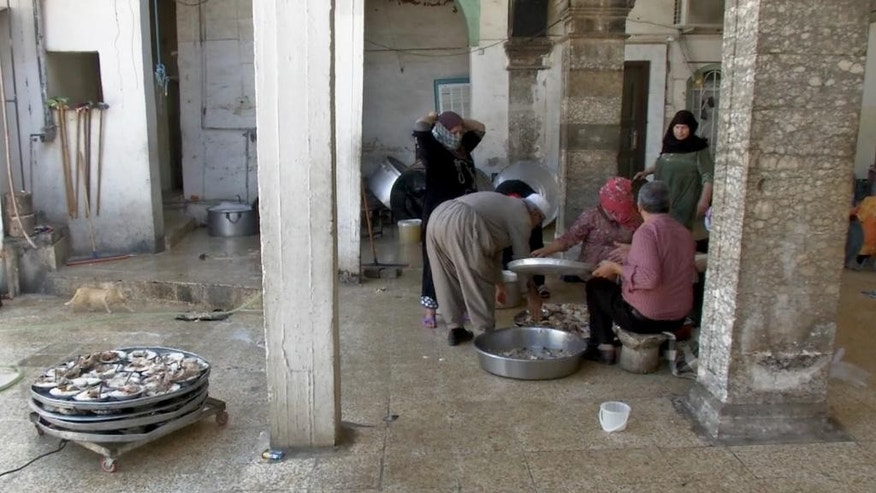 In this image made from AP video taken on Tuesday, April 5, 2016, volunteers at the Shrine of Sheikh Chouli cook for needy people at the Kurdish regional capital, Irbil, Iraq. All are served, including Bangladeshi street cleaners and even locals of modest means, who believe the food is blessed. But the displaced have swelled their ranks. Before the Islamic State group swept across northern and western Iraq in 2014, around 100 people would line up for food each morning. Since then the number has tripled. (AP Photo/Balint Szlanko via AP Video)