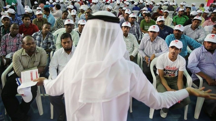 A Senior Administrator from the Dubai Labor Office, speaks to several hundred workers, gathered at a residential camp for laborers and managers during an event, in Abu Dhabi, United Arab Emirates, Wednesday, April 6, 2016. An event aimed at showcasing how the United Arab Emirates is trying to make labor laws more understandable for its vast population of foreign workers found laborers still troubled by abuses and poor conditions. (AP Photo/Kamran Jebreili)