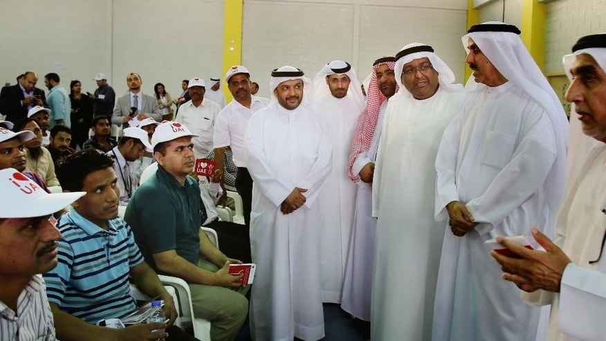 Saqr Ghobash, the UAE's minister of human resources and Emiratization, second right, meets with workers gathered at a residential camp for laborers and managers during an event, in Abu Dhabi, United Arab Emirates, Wednesday, April 6, 2016. An event aimed at showcasing how the United Arab Emirates is trying to make labor laws more understandable for its vast population of foreign workers found laborers still troubled by abuses and poor conditions. (AP Photo/Kamran Jebreili)