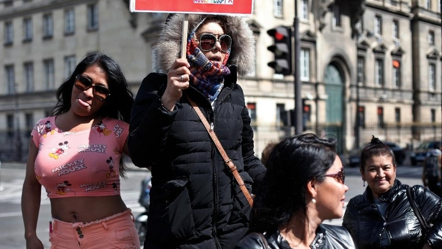 Sex workers hold signs during a protest against new bill against prostitution and sex trafficking, in Paris, Wednesday, April 6, 2016. France's lower house of parliament holds a final vote on Wednesday on a bill against prostitution and sex trafficking that bans buying sex, not selling it. Customers would face fines and be required to attend classes on the harms of prostitution. Opponents fear that cracking down will push prostitutes to hide and they would be even more at the mercy of pimps and violent clients. (AP Photo/Thibault Camus)