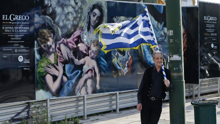 A demonstrator holding a Greek flag joins a protest against Greece's creditors in Athens, Monday, April 4, 2016, as Greece's government started new talks with bailout creditors amid a dispute over a wiretapped and leaked conversation between foreign officials involved in the Greek bailout negotiations. The main sticking points are mandated pension cuts, tax reforms and future cuts Greece must make to meet bailout targets. The country has depended on bailouts since 2010. (AP Photo/Lefteris Pitarakis)
