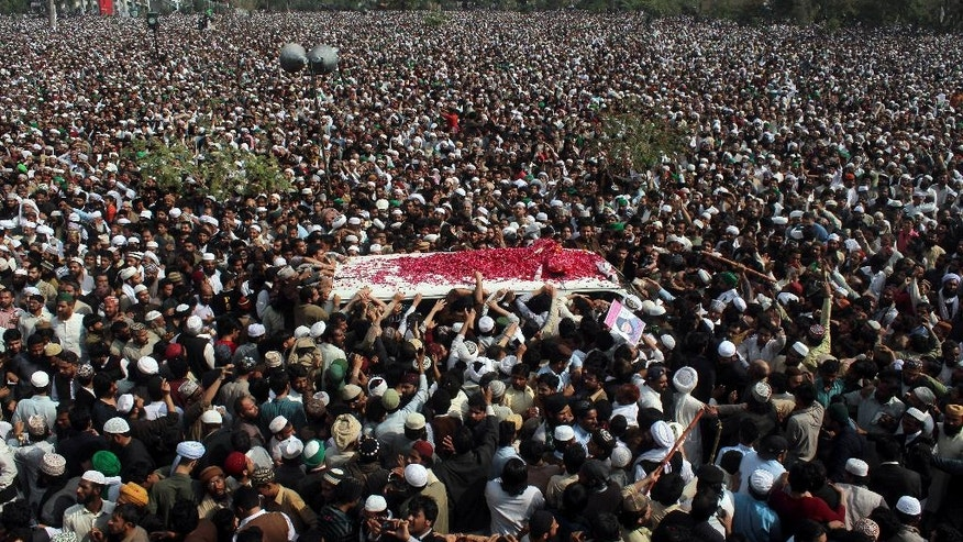 FILE- - In this March 1, 2016 file photo, thousands of people attend a funeral of Pakistani police officer Mumtaz Qadri, the convicted killer of a former governor, in Rawalpindi, Pakistan. Tackling extremists is a political minefield in Pakistan, where politicians openly consort with leaders of banned militant groups, and sympathy exists within the security forces and civil administration for perpetrators of crimes committed in the name of religion. As a result, many remain skeptical of the state's ability to put an end to the militant violence that kills hundreds of Pakistani civilians each year. (AP Photo/Anjum Naveed, File)