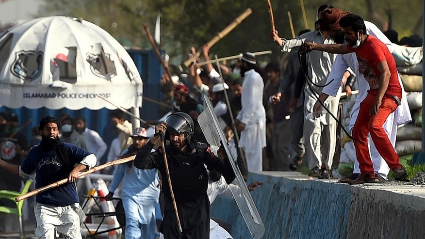 FILE- In this March 27, 2016 file photo, Pakistani religious protesters beat a paramilitary soldier during clashes near the parliament building in Islamabad, Pakistan. Tackling extremists is a political minefield in Pakistan, where politicians openly consort with leaders of banned militant groups, and sympathy exists within the security forces and civil administration for perpetrators of crimes committed in the name of religion. As a result, many remain skeptical of the state's ability to put an end to the militant violence that kills hundreds of Pakistani civilians each year.  (AP Photo/Anjum Naveed, File)