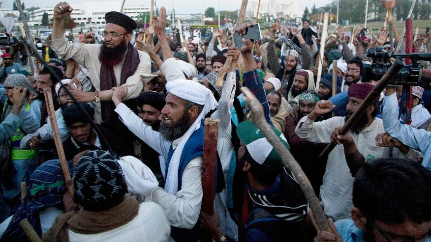 FILE- In this Wednesday, March 30, 2016 file photo, protesters from the Pakistani religious group Sunni Tehreek celebrate the success of a negotiations with government, in Islamabad, Pakistan. Tackling extremists is a political minefield in Pakistan, where politicians openly consort with leaders of banned militant groups, and sympathy exists within the security forces and civil administration for perpetrators of crimes committed in the name of religion. As a result, many remain skeptical of the state's ability to put an end to the militant violence that kills hundreds of Pakistani civilians each year. (AP Photo/B.K. Bangash, File)