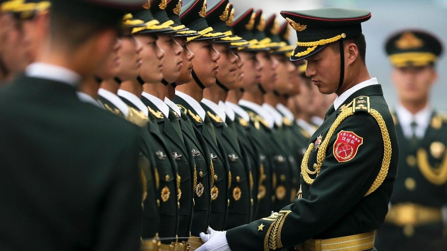 FILE - In this March 21, 2016, file photo, a Chinese People's Liberation Army soldier checks a line of an honor guard as they prepare for a welcome ceremony for visiting German President Joachim Gauck outside the Great Hall of the People in Beijing. The United States, with $596 billion in defense spending, and China, with an estimated $215 billion, led all countries in 2015, the annual report released Tuesday, April 5, 2016, by Stockholm International Peace Research Institute said. Saudi Arabia, however, came in third with spending of $87.2 billion _ double what it spent in 2006, according to the report. That fueled the first worldwide increase in military spending since 2011. (AP Photo/Andy Wong, File)