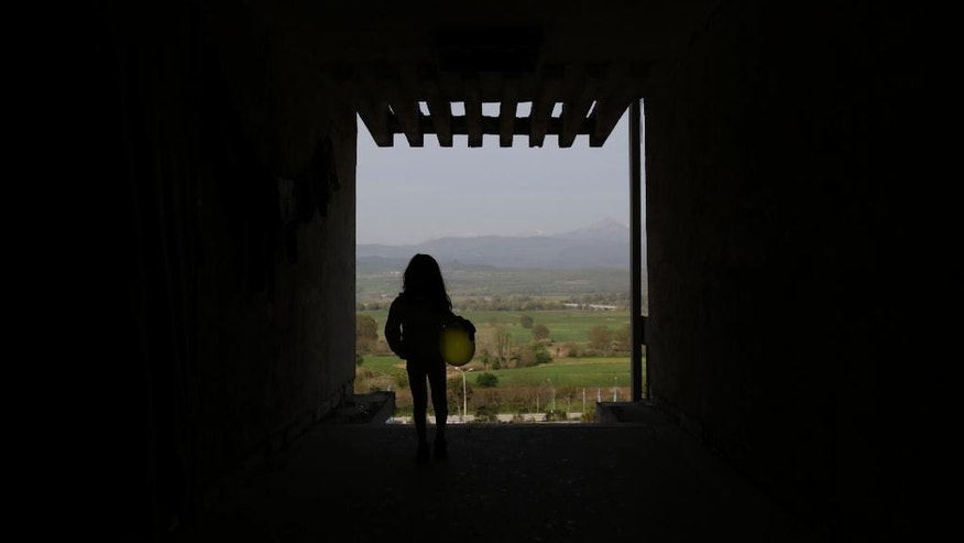 A migrant girl stands in a doorway with a view  on Macedonian mountains near the official Greek - Macedonian border station in Evzoni, Greece, Wednesday, April 6, 2016. Stranded migrants chosen to spend their days in an abandoned building near the official Greek - Macedonian border station in Evzoni, Northern Greece waiting for borders to be opened and living in conditions without running water or electricity under tent or in abandoned building.  (AP Photo/Amel Emric)