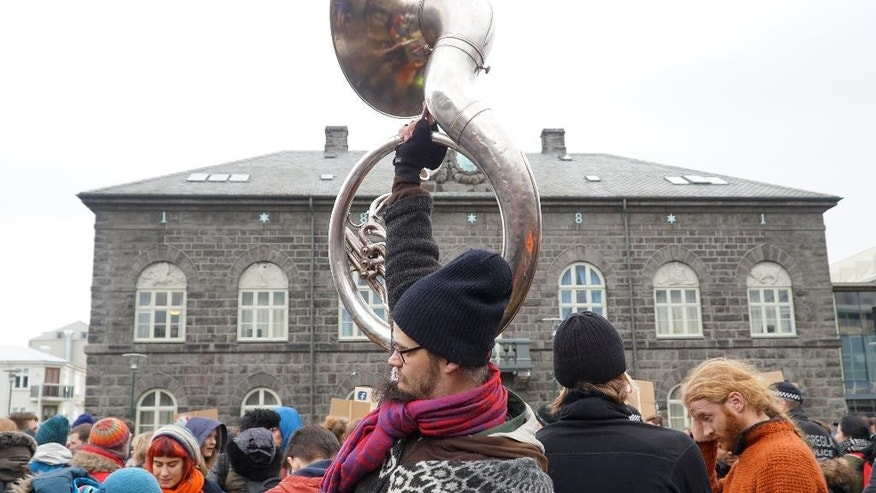 People protest in front of Parliament building in Reykjavik, Iceland, Tuesday April 5, 2016. The leak of millions of records on offshore accounts claims its first high-profile victim as Iceland's prime minister Sigmundur David Gunnlaugsson resigns amid outrage over revelations he used such a shell company to conceal a conflict of interest. (AP Photo/David Keyton)