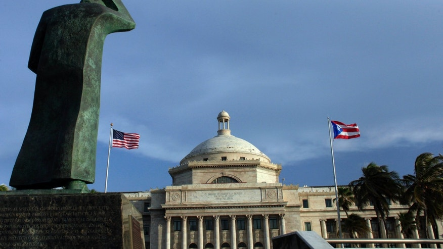 In this Wednesday, July 29, 2015 photo, a bronze statue of San Juan Bautista stands in front of Puerto Rico's Capitol as U.S. and Puerto Rican flags fly in San Juan, Puerto Rico. Mired in an ongoing economic crisis the government has tried to boost revenue by hiking the sales tax to 11.5 percent, higher than any U.S. state, and closing government offices. (AP Photo/Ricardo Arduengo)