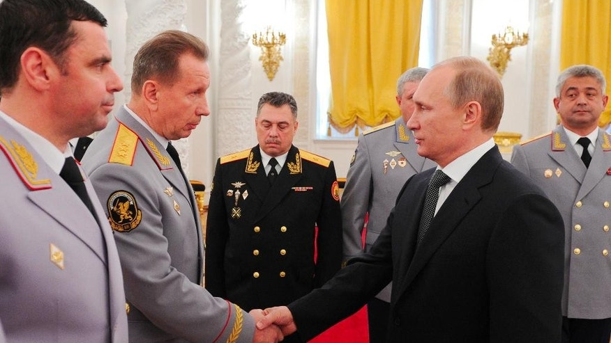 FILE In this Friday, Oct. 31, 2014 file photo Russian President Vladimir Putin, right, shakes hands with then Interior Troops Commander Viktor Zolotov at a meeting with senior officers in the Kremlin  in Moscow, Russia. Putin has ordered the creation of a new law enforcement agency, the National Guards, which will be led by their commander, Putin's former chief bodyguard, Viktor Zolotov. (Mikhail Klimentyev/Sputnik, Kremlin Pool Photo via AP, file)