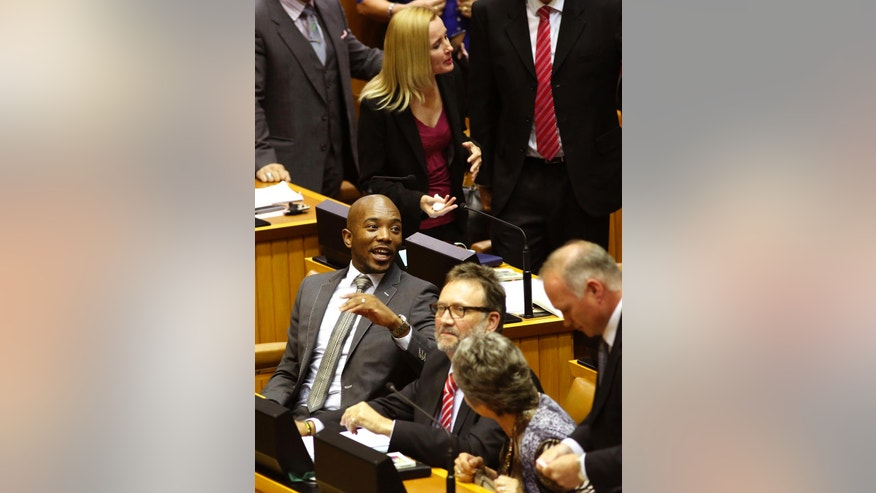 Mmusi Maimane, left, leader of the official opposition party in South Africa, the Democratic Alliance party, DA, interacts with other party members before a parliament session starts in Cape Town, South Africa, Tuesday, April 5,  2016.  A South African parliamentary debate over whether to remove President Jacob Zuma was delayed Tuesday after opposition lawmakers alleged that the parliament speaker, a Zuma ally, could not preside over the session because of alleged partiality. (AP Photo/Schalk van Zuydam)
